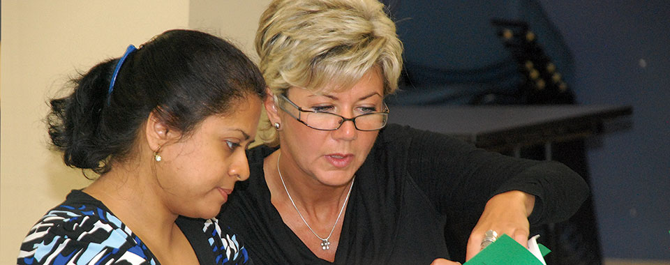 A woman with glasses teaches another woman at WHSC Training session.