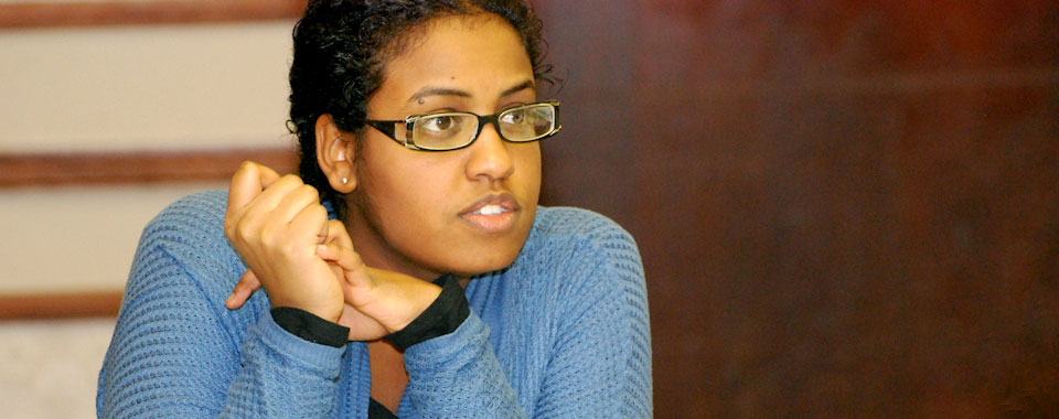 A young woman with glasses listens at a WHSC training course.