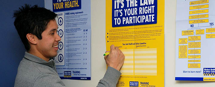 Worker reviews WHSC health and safety posters on the right to know, right to participate and right to refuse unsafe work