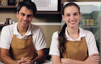 A smiling young man and woman wearing aprons