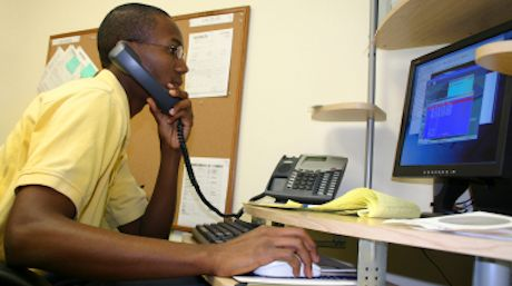 a WHSC employee answering a phone call and reading information on a computer screen